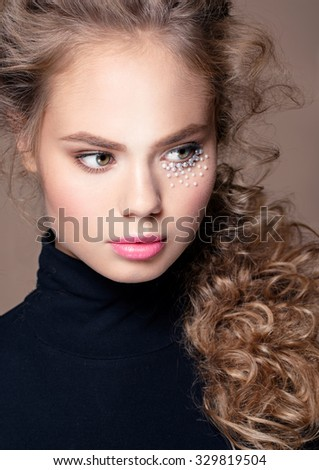 Woman portrait with art make up pearls, curly hairstyle