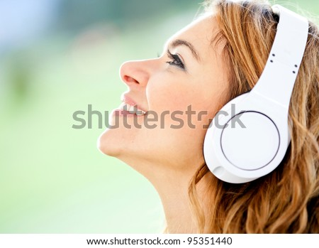 Woman portrait with headphones listening to music - stock photo