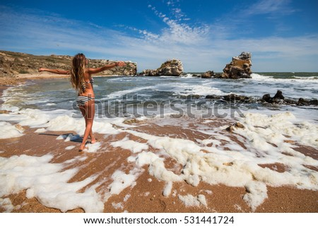 Woman poses in swimsuit on beah of sea and looks at sea, back view