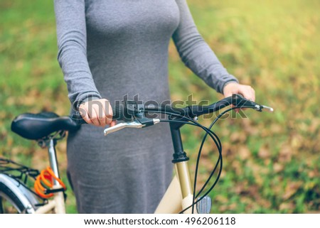 Woman poses with her bicycle in park during autumn. Unrecognizable attractive young adult female with vintage retro bike, cycling or commuting, ecological transportation concept.