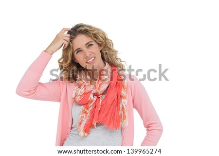 Woman posing and smiling while scratching her head on white background - stock photo