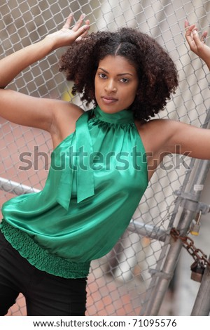 Woman posing by the fence - stock photo