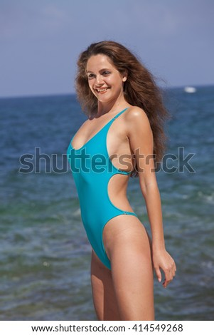 Woman posing in a modish swimsuit on the beach - stock photo