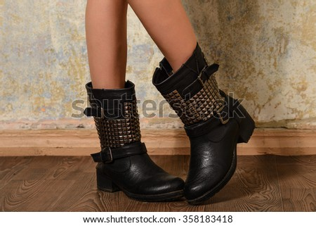 Woman posing in black autumn boots with spikes and studs