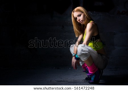 Woman posing in dark urban environment  - stock photo