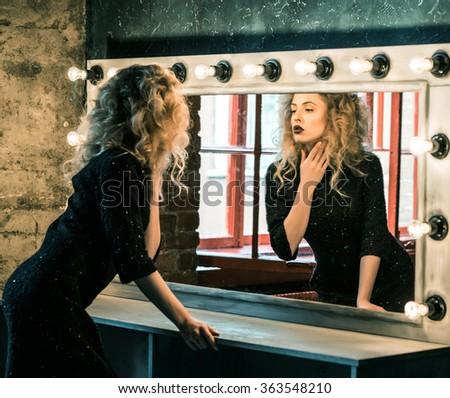 woman posing near the mirror - stock photo