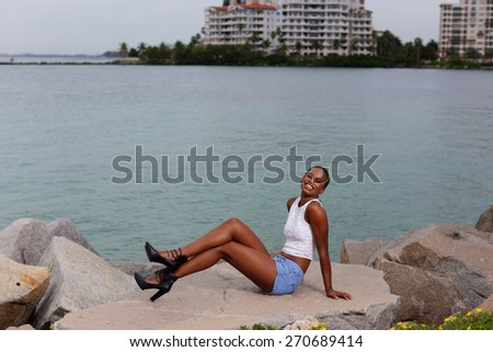 Woman posing on rocks by the water - stock photo