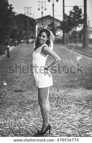 Woman posing on streets after sunset
