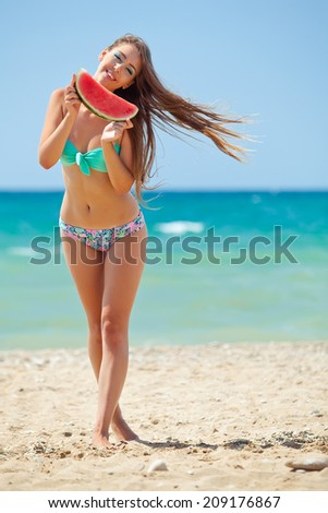 Woman posing on the beach and eating watermelon