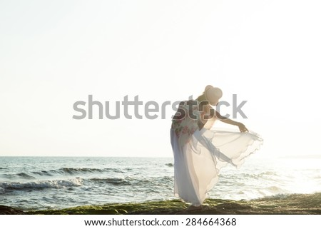 Woman posing on the beach at the sunset - stock photo