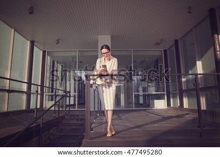 Woman posing outside an office building in summer business outfit