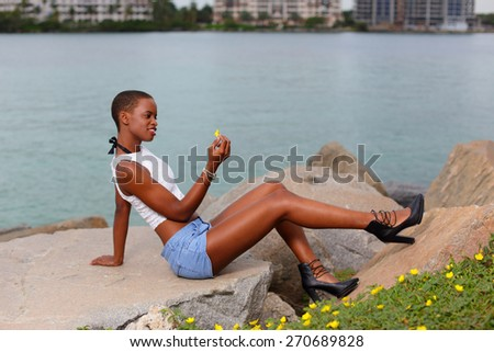Woman posing with a daisy on the rocks - stock photo