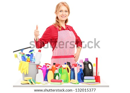 Woman posing with cleaning supplies and giving a thumb up isolated on white background