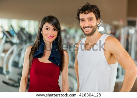 Woman posing with her fitness trainer in the gym - stock photo