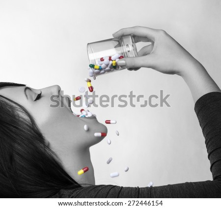 woman pouring a glass full of pill down her throat  - stock photo