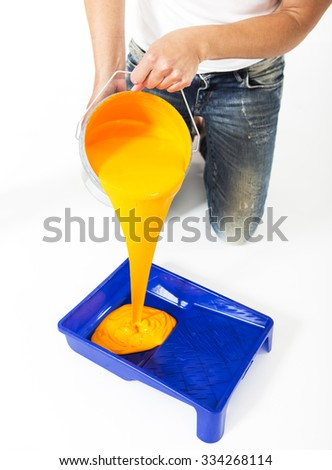 Woman pouring color into a roller pan on white background - stock photo