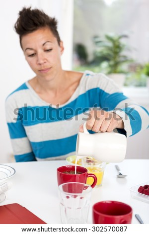 Woman pouring milk in her morning coffee at the breakfast table.