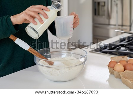 Woman pouring milk in measuring jug flour in glass bowl