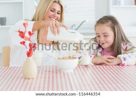 Woman pouring milk into a glass for daughter and smiling - stock photo