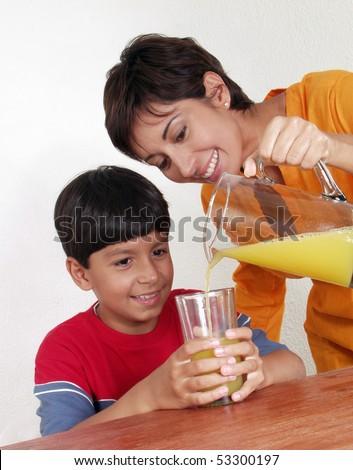 woman pouring orange juice to a boy. - stock photo