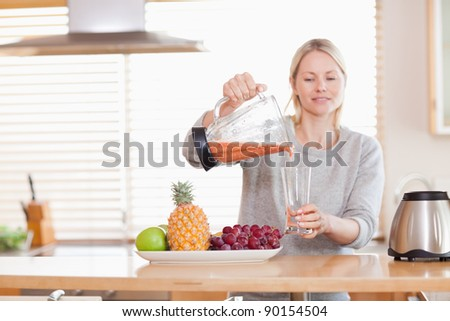 Woman pouring self made fruit juice into a glass - stock photo