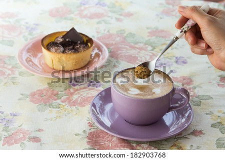 woman pouring sugar spoon into a hot cup of coffee - stock photo