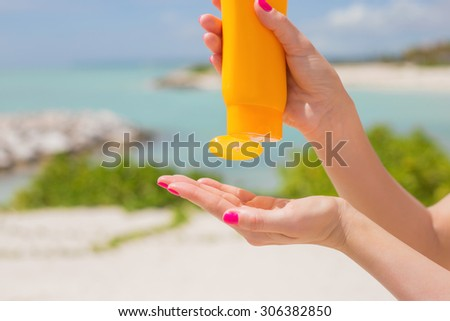 Woman pouring sunscreen in hand - stock photo