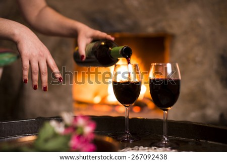 Woman pouring wine to the wine glasses in front of the fireplace. - stock photo