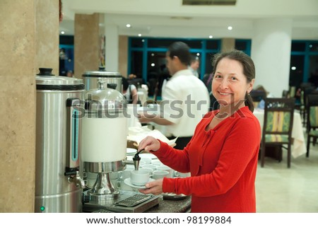 Woman pours milk to coffee at hotel restaurant