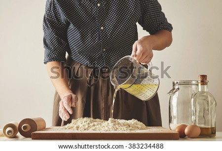 Woman pours water with olive oil from measure cup to flour on board, to prepare dough for pasta or dumplings. Cooking guide presentation - stock photo