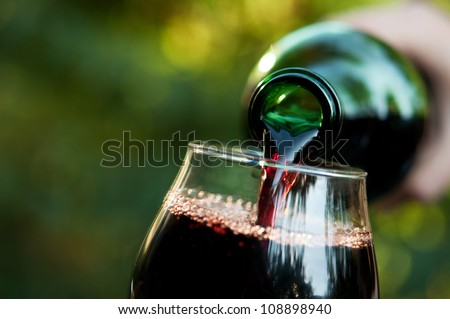 Woman pours wine into a glass background - stock photo