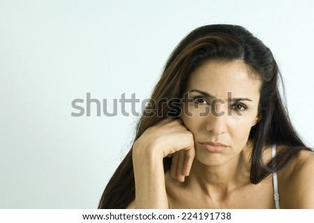 Woman pouting, looking at camera, portrait - stock photo