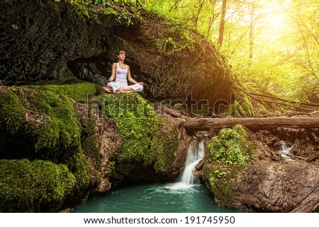 Woman practices yoga in nature, the waterfall. sukhasana pose - stock photo