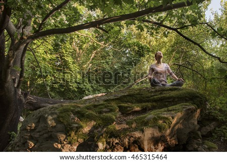 woman practices yoga in the woods.