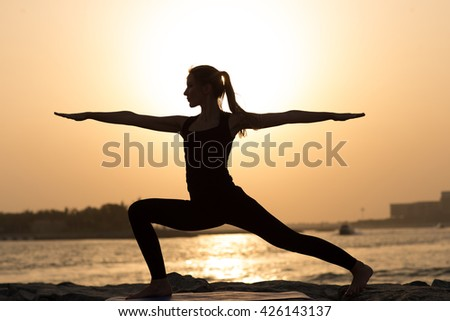 woman practices yoga on a background of sea sunset