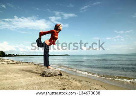 Woman practicing a yoga balance by the sea - stock photo