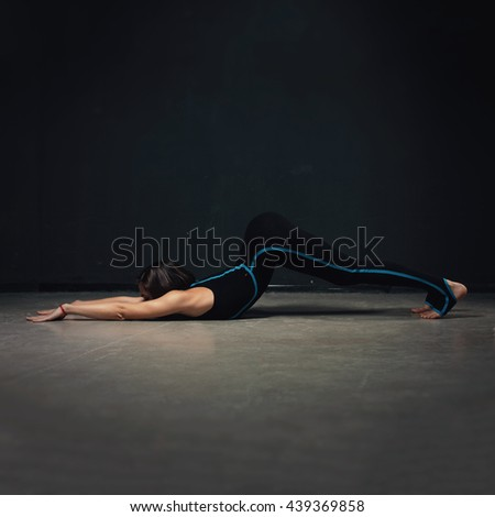 Woman practicing advanced yoga against a dark texture wall - stock photo