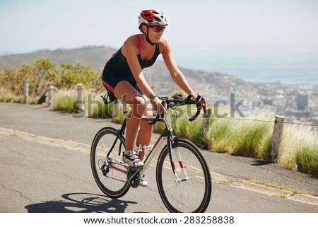 Woman practicing for triathlon competition. Triathlon athlete cyclist down hill on country road. Young woman riding bicycle on open road. - stock photo
