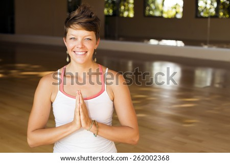 Woman practicing meditation at a yoga studio - stock photo