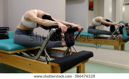 Woman practicing Pilates on the Reformer. - stock photo