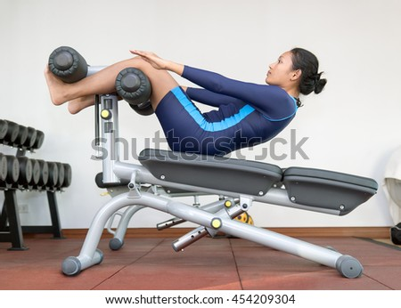 Woman practicing sit-ups on exercise machines at the gym. - stock photo