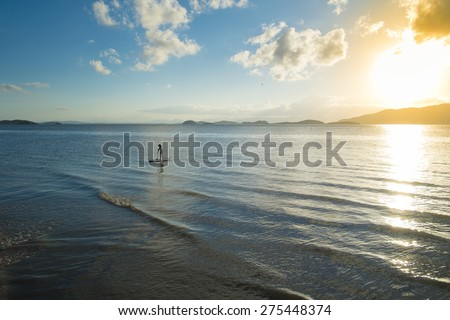 Woman practicing Stand up Paddle in a beautiful sunset at Sao Francisco do Sul, Santa Catarina State, Brazil. Clouds, Sun and Blue Sky make the perfect combination - stock photo