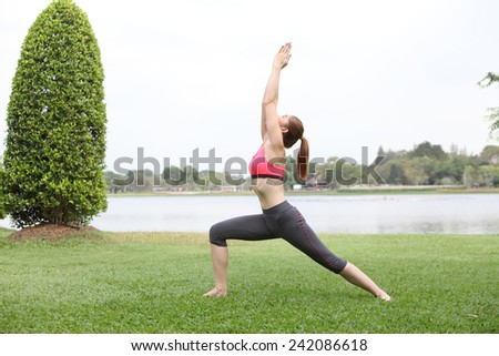 Woman practicing Warrior yoga pose outdoors on lawn,left side - stock photo