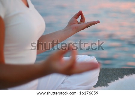 Woman practicing yoga at sunset - stock photo