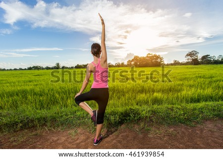 Woman practicing yoga at the meadow
