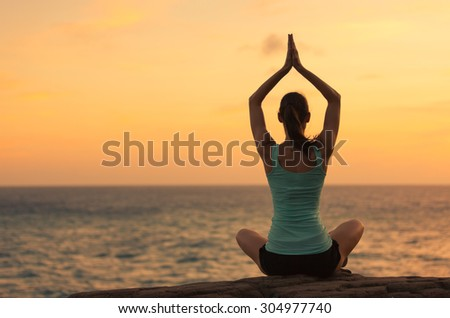 Woman practicing yoga by the sea.