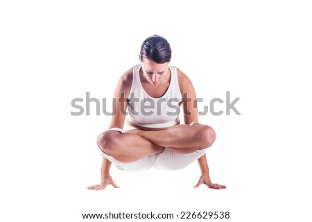 "Woman practicing yoga doing the ""Scale pose lotus variation"" posture. Tolasana - stock photo"