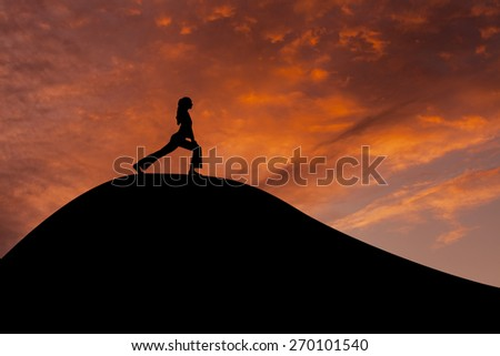 Woman practicing yoga during sunset - stock photo