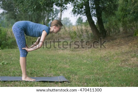 woman practicing yoga in a summer park