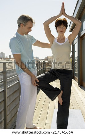 Woman practicing yoga, man standing beside her - stock photo